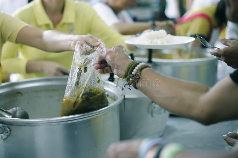 可怜的人民从捐款人接受捐赠的食物,展示相互分享在今天社会:帮助贫穷的概念 库存照片
