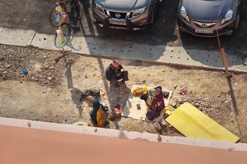 可怜的印度人民吃在街道上的午餐在新德里 ?? r 免版税库存照片