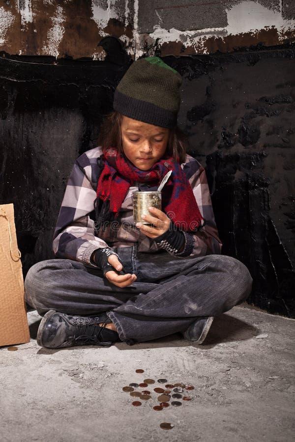 可怜的叫化子儿童男孩回顾他收到的金钱 免版税库存图片