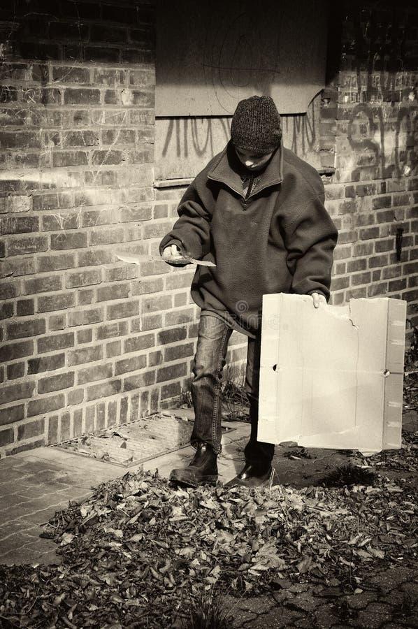 可怜的叫化子男孩在后院,他的家 免版税库存照片