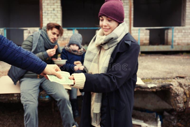 可怜的年轻女人和她的家庭乞求为金钱 免版税图库摄影