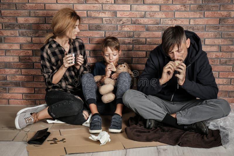 可怜的无家可归的家庭坐地板 免版税库存图片