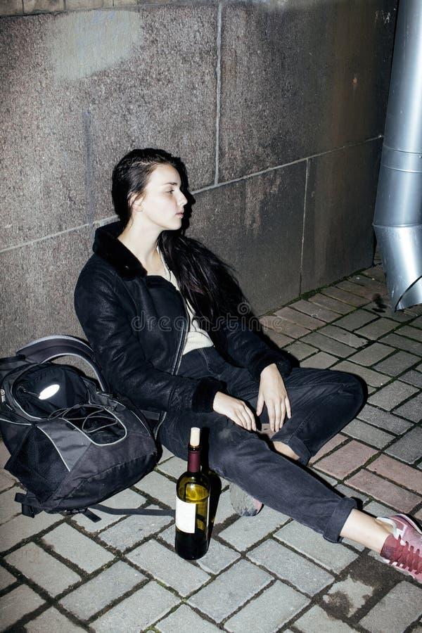 年轻可怜的ttenage女孩在肮脏的墙壁坐与瓶的地板藤,可怜的难民酒客,绝望的无家可归者 图库摄影