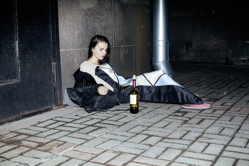 年轻可怜的ttenage女孩在肮脏的墙壁坐与瓶的地板藤,可怜的难民酒客,绝望的无家可归者 免版税库存图片