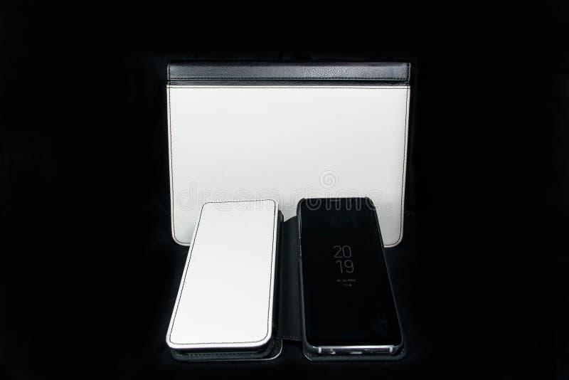可折叠的电话和片剂装入在黑backgroud的白色和黑皮革空白升华印刷品设计的 免版税库存照片