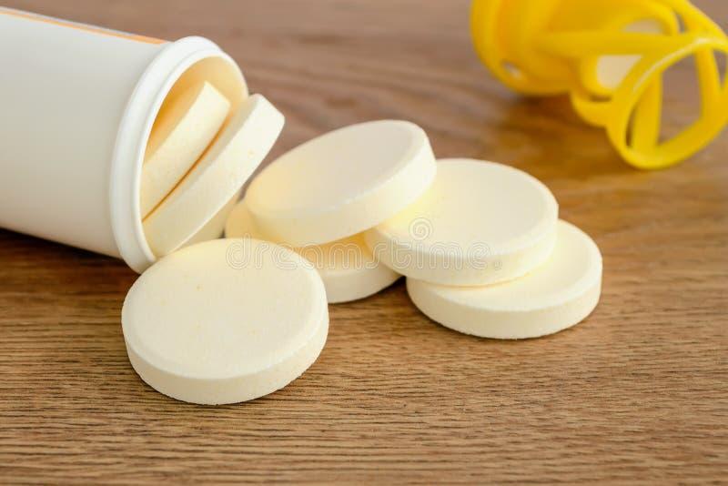 可溶解冒泡维生素药片溢出在木背景的塑料瓶外面 维生素和营养补充 图库摄影