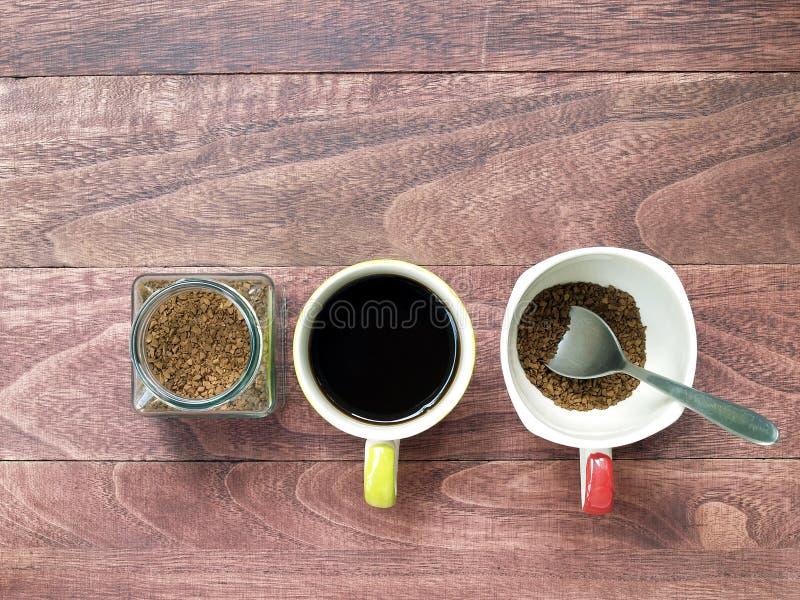 可溶解速溶咖啡粉末在透明玻璃瓶子和一个杯子无奶咖啡中和准备酿造有匙子的另一个杯子 免版税库存照片