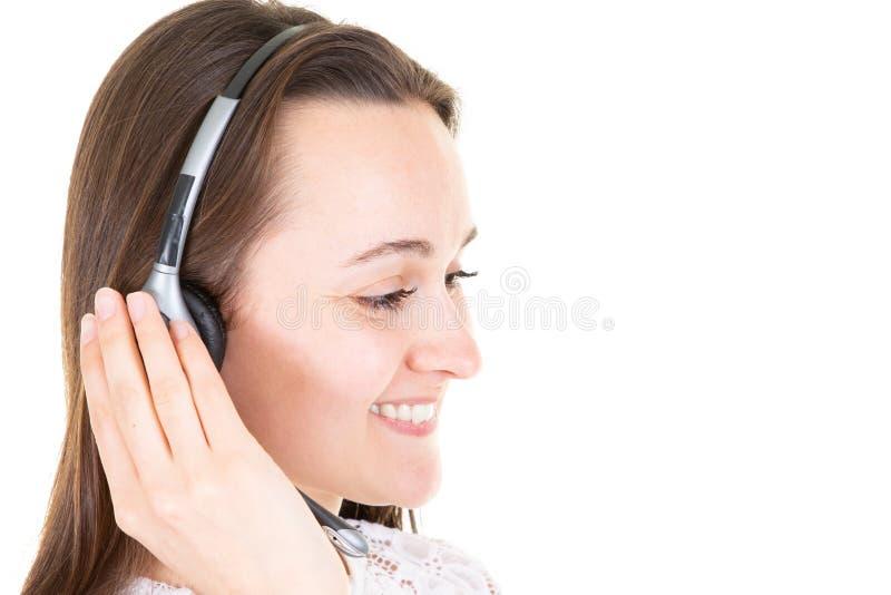 可爱和美丽的年轻女人边画象电话中心代理讲话与某人在她的被隔绝的面孔的耳机微笑的  免版税库存照片