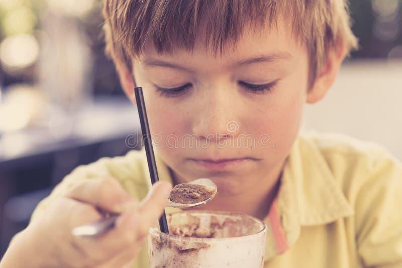 可爱和美好的小孩7或8岁顶头画象在享用愉快的饮用的冰淇凌圆滑的人的黄色衬衣的挤奶shak 图库摄影