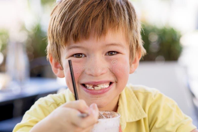 可爱和美好的小孩7或8岁顶头画象在享用愉快的饮用的冰淇凌圆滑的人的黄色衬衣的挤奶shak 免版税图库摄影