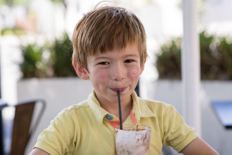 可爱和美好的小孩7或8岁顶头画象在享用愉快的饮用的冰淇凌圆滑的人的黄色衬衣的挤奶shak 库存照片