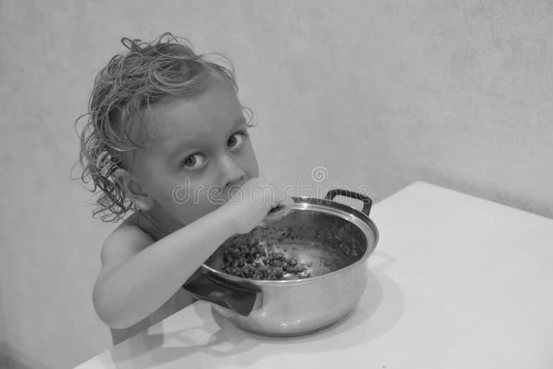 可爱宝贝单独坐和吃在厨房里的4岁 白肤金发的男孩纵向 孩子微笑并且吃 好胃口, 免版税库存照片