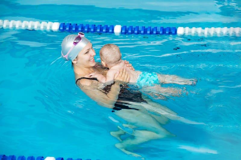 可爱宝贝在与她的母亲的水池学会游泳 库存照片