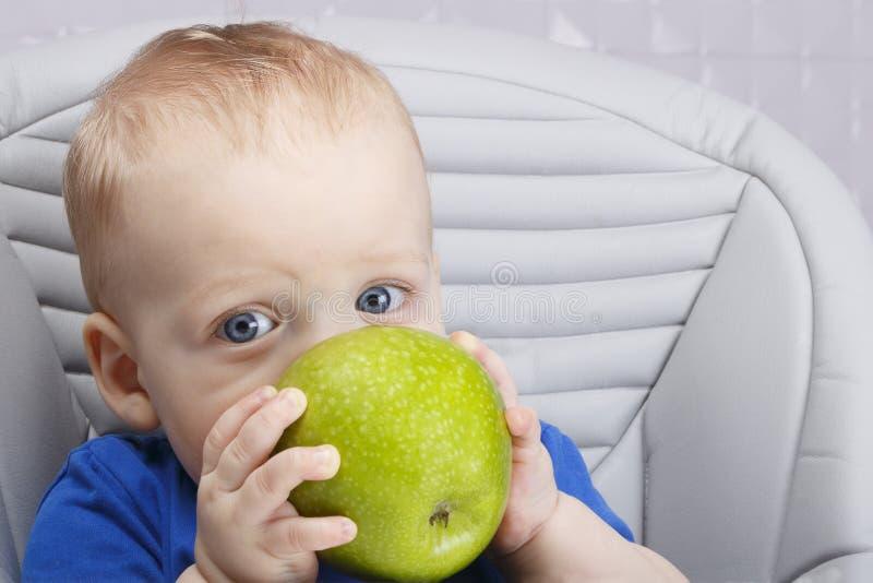 可爱宝贝坐高儿童椅子和吃单独绿色苹果的1,4岁在白色厨房里 图库摄影