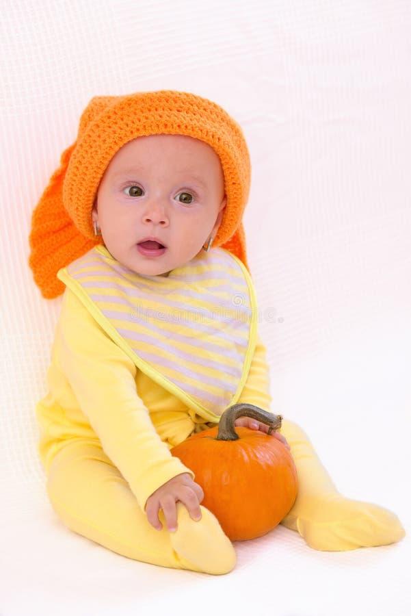 可爱宝贝女孩用南瓜和橙色帽子 免版税库存照片
