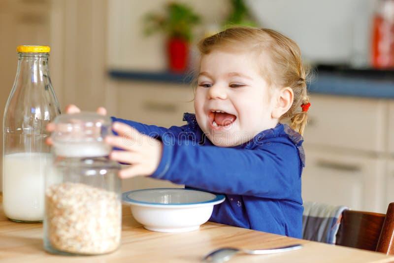可爱小孩女孩吃健康oatmeals用早餐逗人喜爱的愉快的小孩子的牛奶五颜六色衣裳坐的 免版税图库摄影