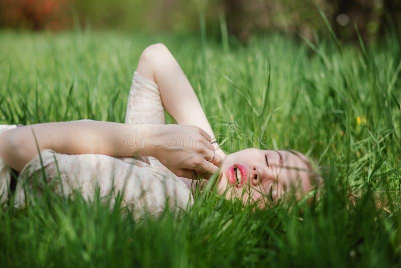 可爱白肤金发说谎在绿草 库存图片