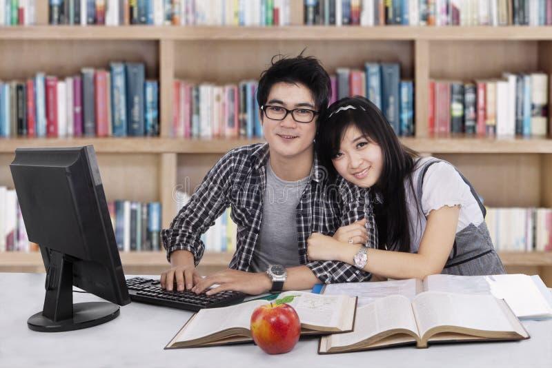 可爱的两学生在图书馆1里 免版税图库摄影