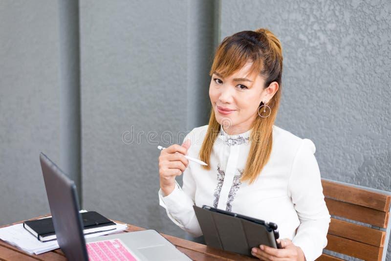 可爱的亚裔中国女孩坐运作在膝上型计算机片剂的公园长椅偶然 免版税库存照片