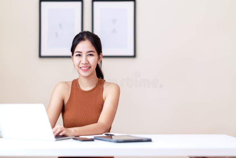 可爱的亚裔企业家妇女、愉快的学生或者年轻执行委员坐穿偶然橙色背心礼服的白色书桌桌 免版税库存图片
