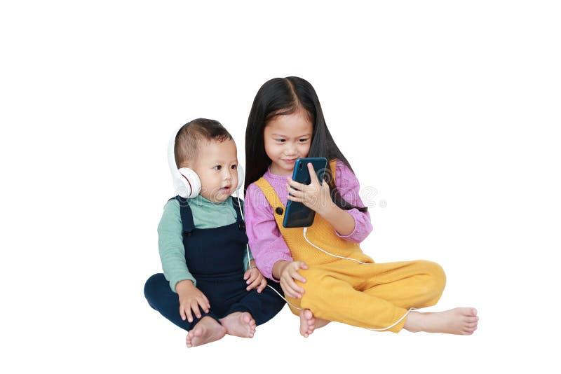 可爱的亚裔分享对的姐姐和弟弟由智能手机享受与耳机的听的音乐被隔绝在白色 免版税库存照片