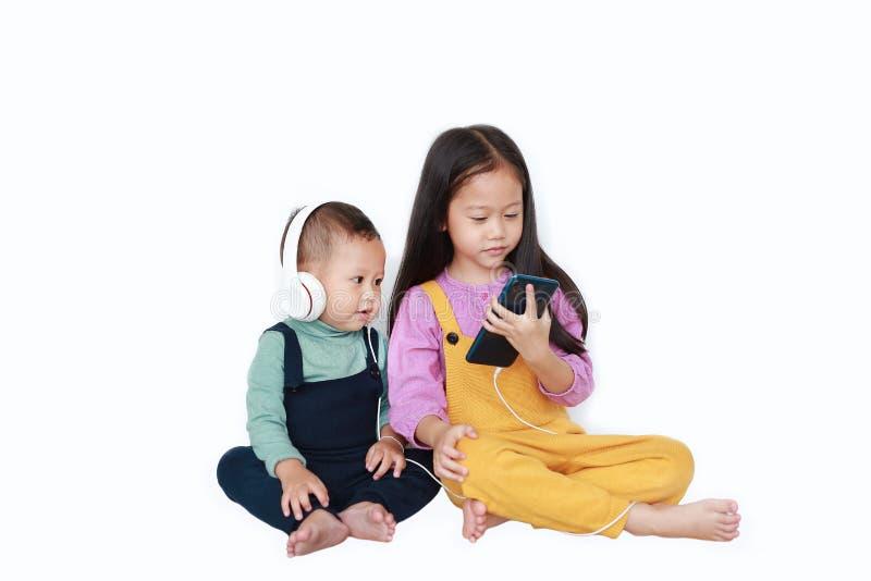 可爱的亚裔分享对的姐姐和弟弟由智能手机享受与耳机的听的音乐被隔绝在白色 库存照片