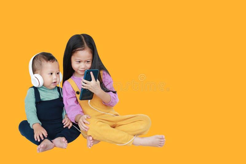 可爱的亚裔分享对的姐姐和弟弟由被隔绝的智能手机享受与耳机的听的音乐  库存照片