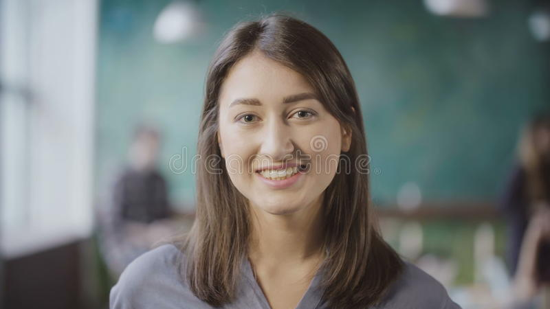 可爱的亚裔女实业家画象在顶楼办公室 成功的女工转过来,神色和微笑 免版税库存图片