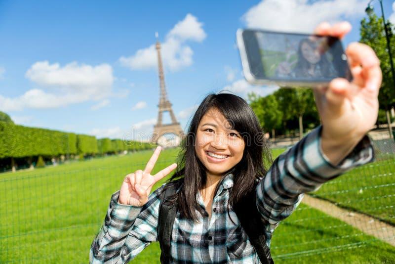 年轻可爱的亚裔游人在采取selfie的巴黎 图库摄影