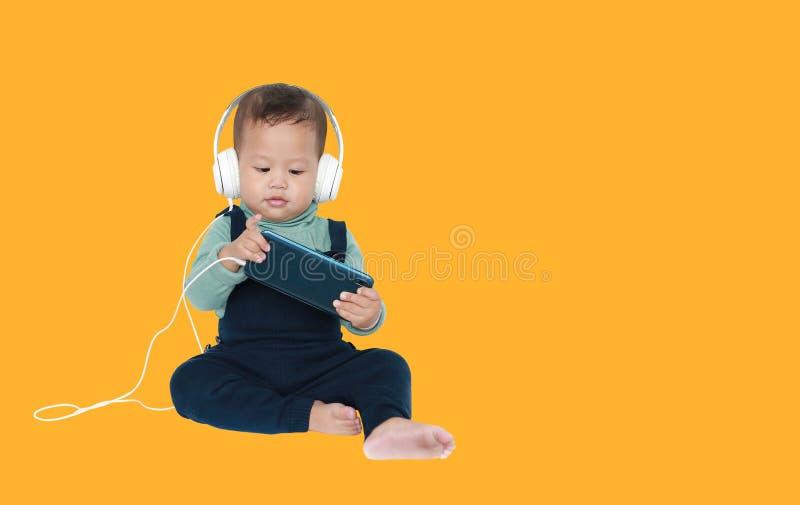 可爱的亚裔矮小的男婴由智能手机享受与耳机的听的音乐被隔绝在黄色背景 库存图片