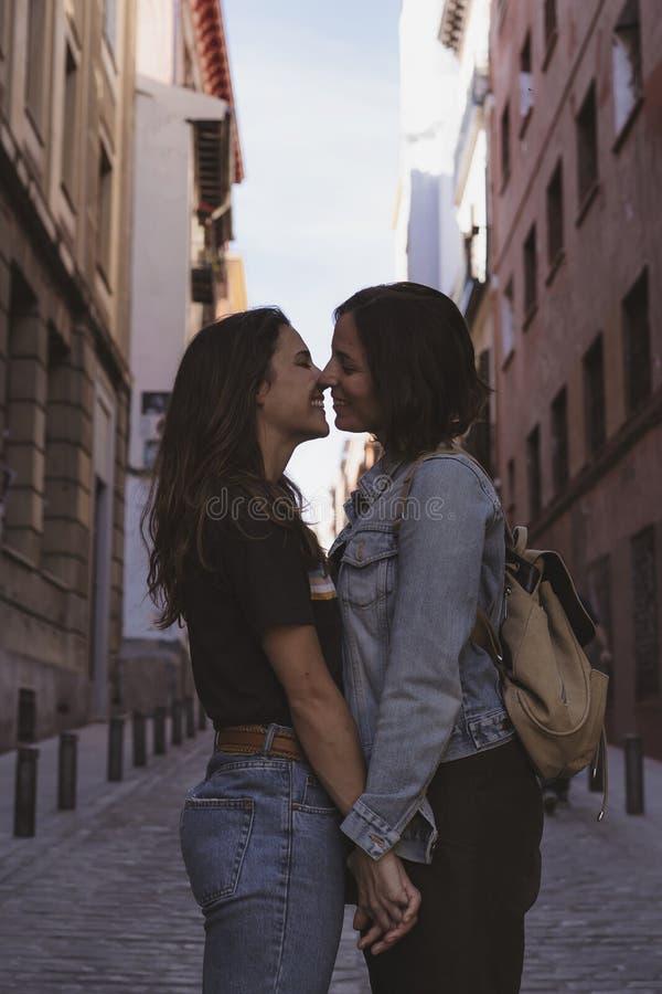 可爱的亲吻和微笑在马德里街道的年轻女人女同性恋的夫妇  库存图片