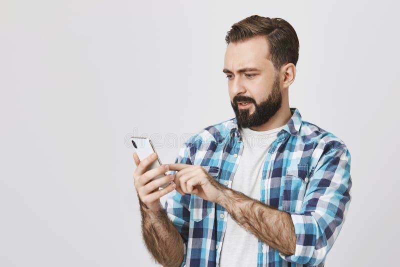 可爱的人和与惊奇和使为难的浏览网络画象有拿着智能手机的胡子和髭的 免版税库存照片