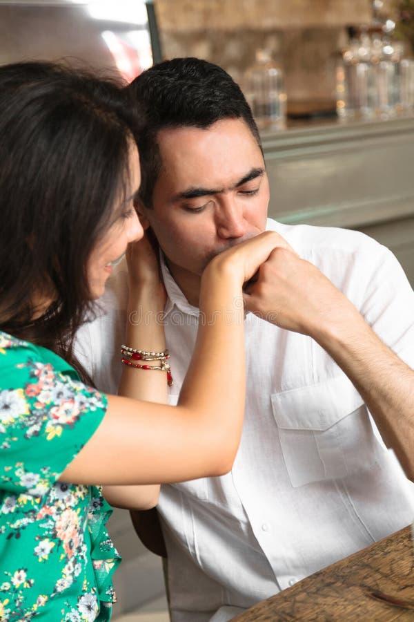 可爱的人轻轻地亲吻他的妻子的手 免版税库存照片