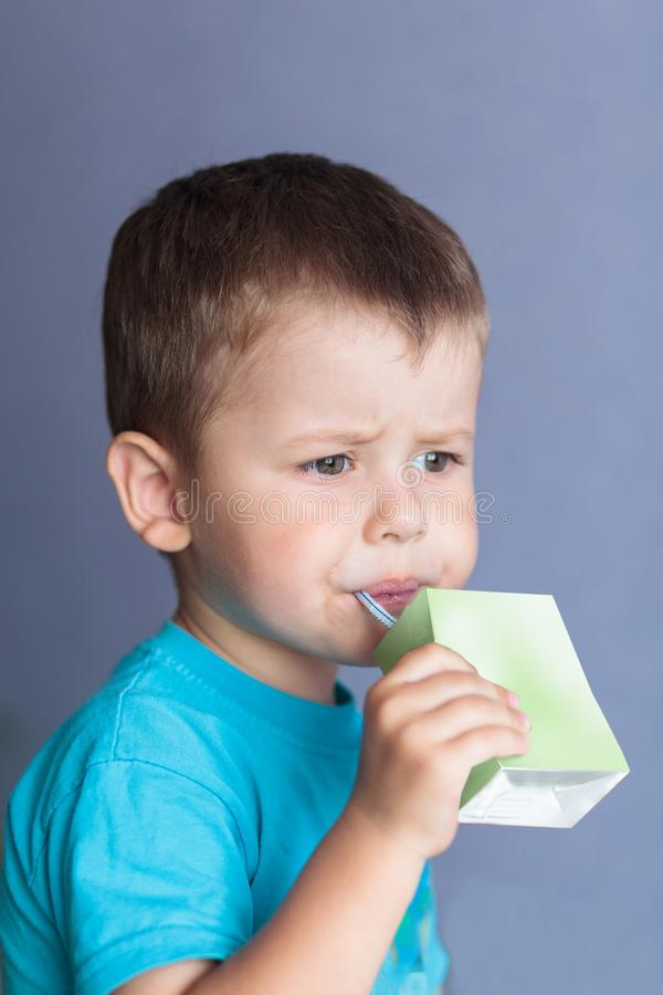 可爱的从秸杆的孩子饮用的汁液 喝汁液箱子的逗人喜爱的小男孩 库存图片