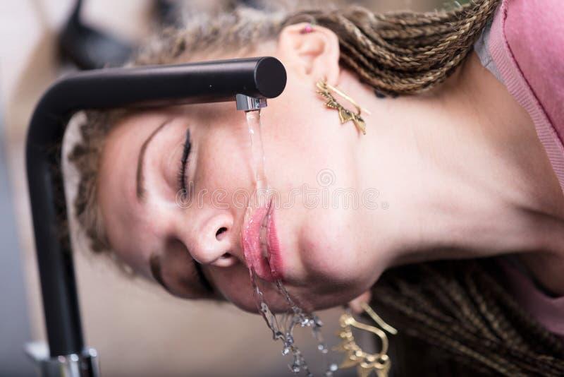 可爱的从轻拍的妇女饮用水 库存照片