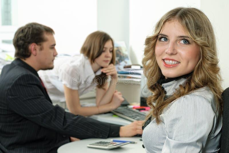 可爱的企业夫人在办公室微笑 免版税图库摄影