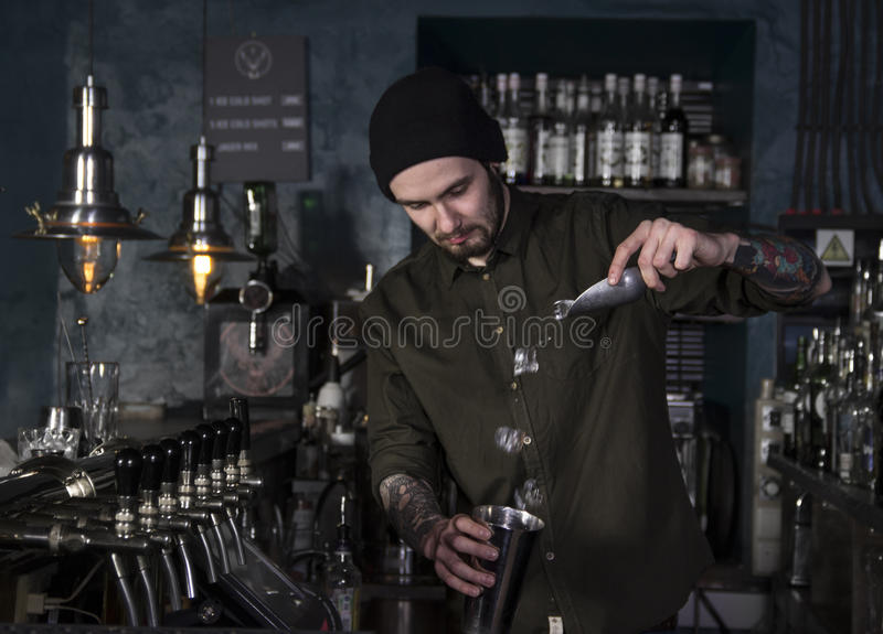 可爱的侍酒者做一个鸡尾酒 免版税图库摄影