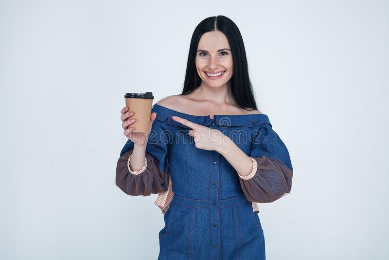 可爱的俏丽的可爱的时髦的好逗人喜爱的快乐的深色的女孩画象牛仔裤的穿戴,指向纸杯子咖啡, 免版税库存图片