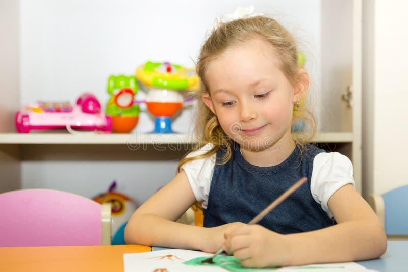 可爱的儿童女孩在托儿所屋子里画一把刷子和油漆 孩子在幼儿园在蒙台梭利幼儿园类 免版税库存图片