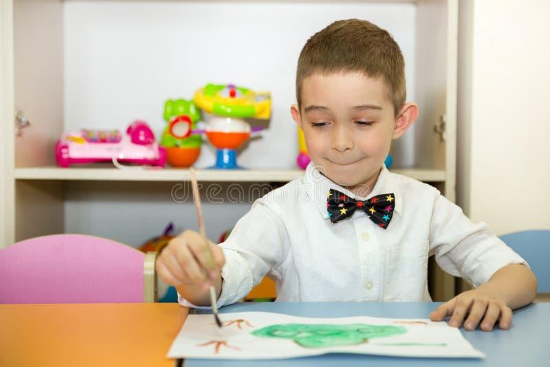 可爱的儿童男孩在托儿所屋子里画一把刷子和油漆 孩子在幼儿园在蒙台梭利幼儿园类 库存照片