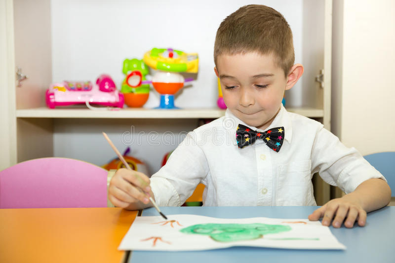 可爱的儿童男孩在托儿所屋子里画一把刷子和油漆 孩子在幼儿园在蒙台梭利幼儿园类 库存图片