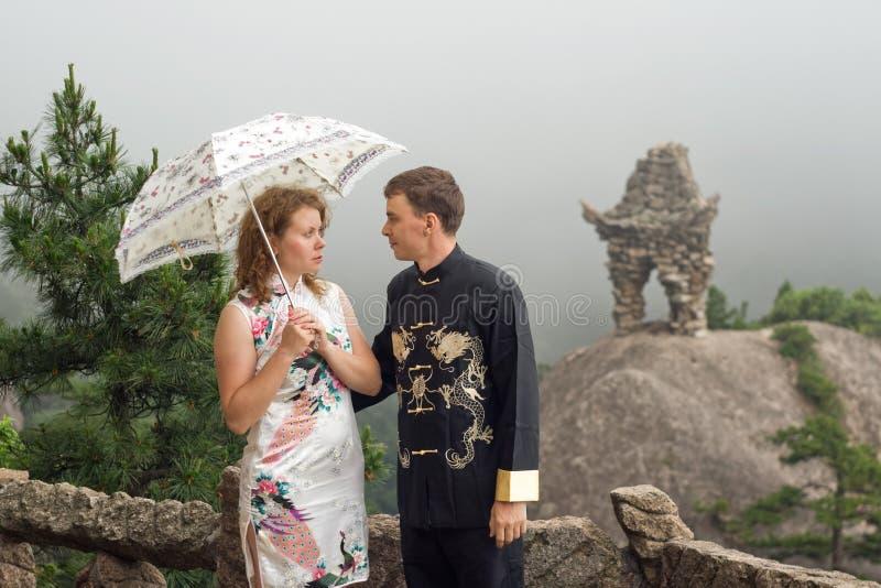 可爱的加上在多云天气的伞在中国山顶部 免版税库存照片