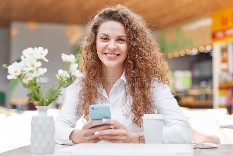 可爱的卷曲妇女照片有微笑的,穿戴在典雅的衣物,读宜人的sms消息,花费在舒适咖啡馆的业余时间 免版税库存照片