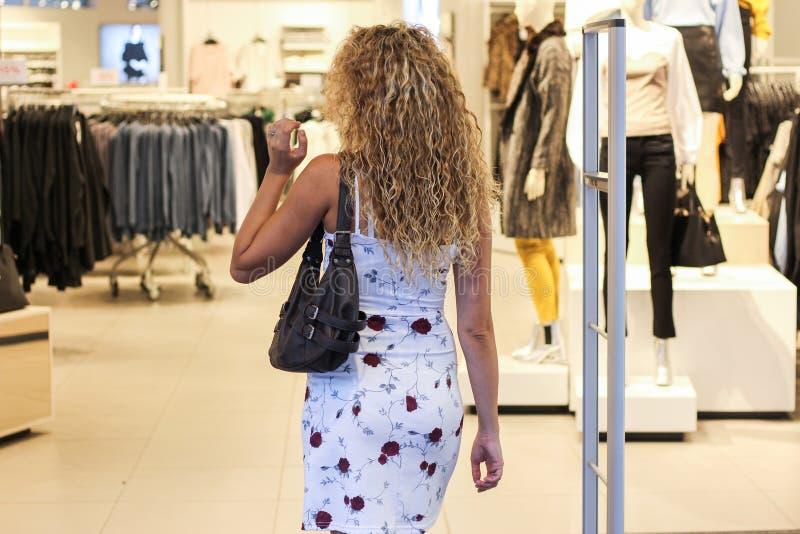 可爱的卷曲白肤金发的女孩输入的时尚和服装店 库存照片