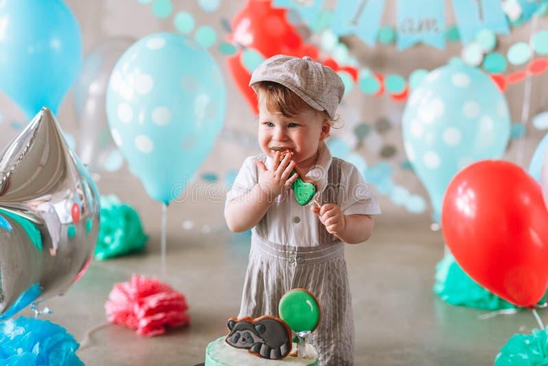 可爱的吃小生日蛋糕的男婴佩带的衣服和帽子在装饰的演播室室 免版税图库摄影