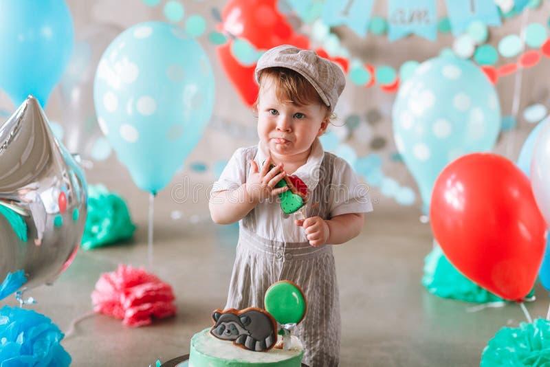 可爱的吃小生日蛋糕的男婴佩带的衣服和帽子在装饰的演播室室 免版税库存图片