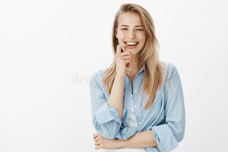 可爱的吸引人白肤金发的女生穿笑快乐尖酸的手指微笑的满意赢得的偶然衬衣 免版税库存图片