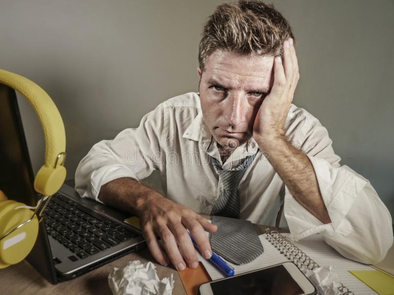 可爱的哀伤和绝望人丢失看杂乱和沮丧工作在营业所PR的便携式计算机书桌的领带 库存图片
