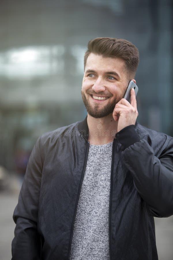 可爱的商人在他巧妙的电话谈话 库存照片
