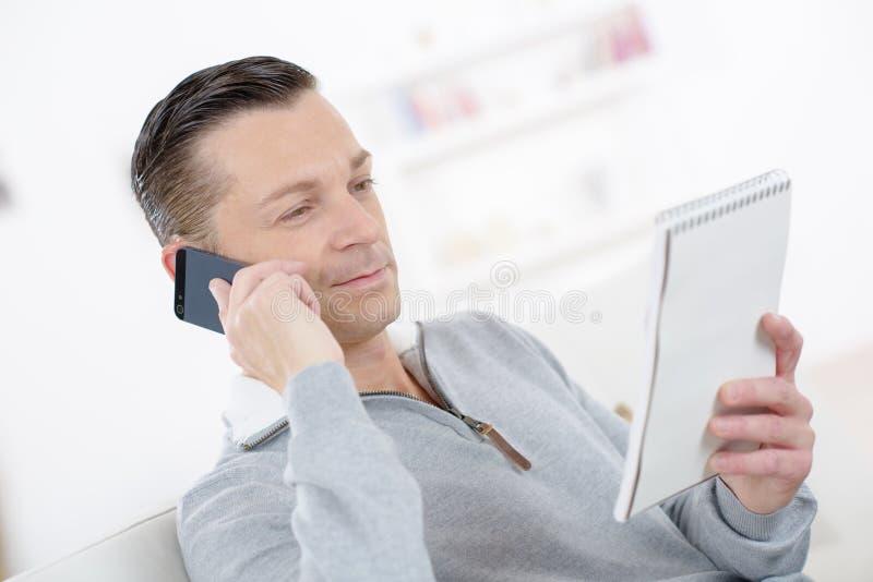 可爱的商人微笑的做注意谈话在电话 免版税库存图片